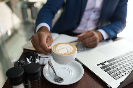 Businessman drinking a cappuccino while working at a cafe table Stok Fotoğraf