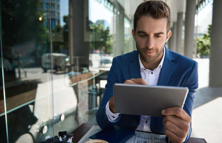 Businessman working on a tablet outside at a cafe table