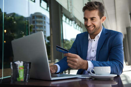 Smiling businessman sitting outside at a cafe table shopping online