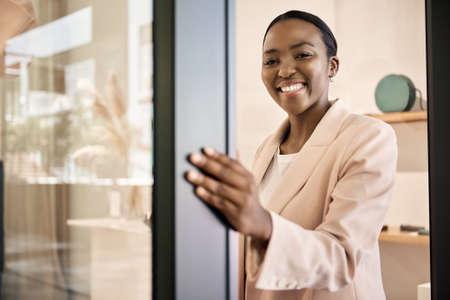 Smiling African American entrepreneur opening the door of her shop Archivio Fotografico
