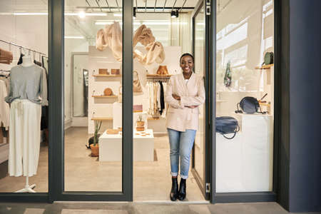 Smiling African American female entrepreneur standing at her shop door 免版税图像