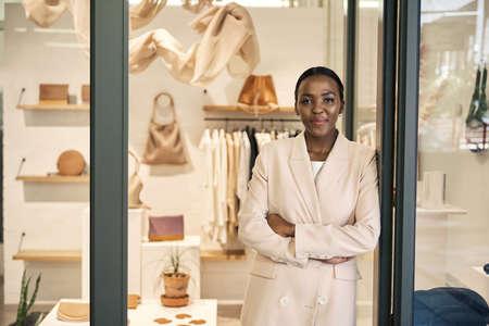 Confident African American female entrepreneur leaning against her shop door 免版税图像