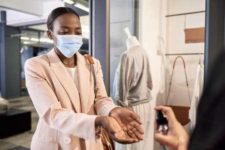 African American shop customer having sanitizer sprayed on her hands