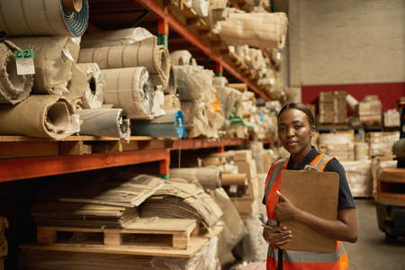 Young African warehouse worker standing by shelves with a clipboard 免版税图像