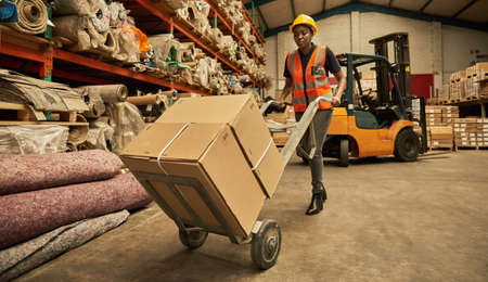 African female warehouse worker moving boxes with a dolly