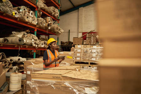 African female warehouse worker checking boxes using a digital tablet