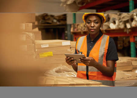 Young African female warehouse worker checking inventory with a tablet