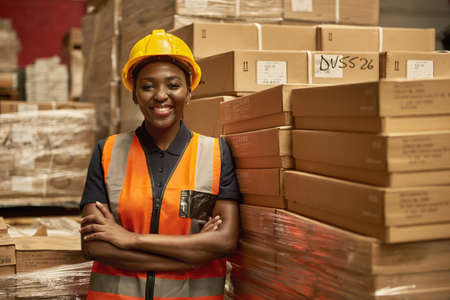 Smiling African female warehouse worker leaning against some boxes 免版税图像