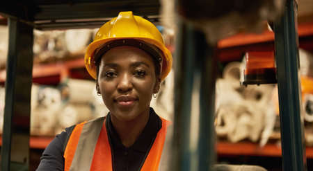 African female forklift operator working in a textile storehouse
