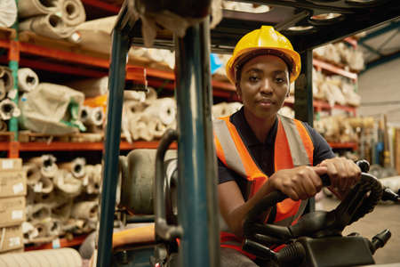 Confident African female forklift operator working in a storehouse