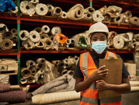 African worker wearing a face mask in a warehouse