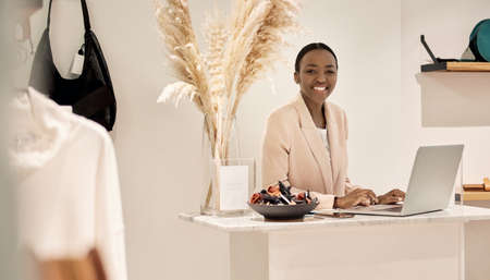 Smiling African American entrepreneur using a laptop in her shop