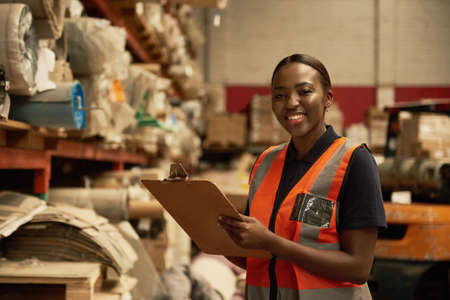 Smiling young African female warehouse worker doing inventory