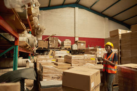 African female warehouse worker checking inventory with a digital tablet 免版税图像