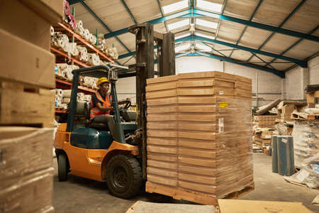 African female forklift operator moving boxes around a warehouse