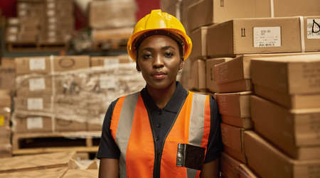 Young African female warehouse worker standing by stacks of boxes