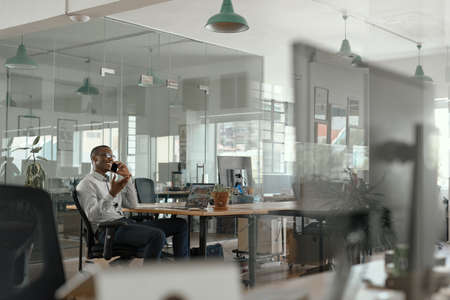 Smiling African businessman talking on his phone in an office
