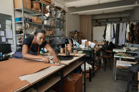 African female artisan cutting leather at a workshop bench