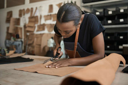 Young African female artisan cutting leather in her workshop Banque d'images