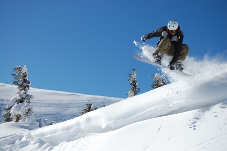 Snowboarder jumping from a cliff in snow powder Ukraine, Carpathians, Dragobrat