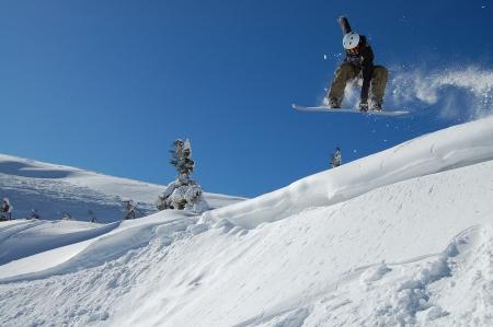 Snowboarder jumping from a cliff in snow powder  Ukraine, Carpathians, Dragobrat photo