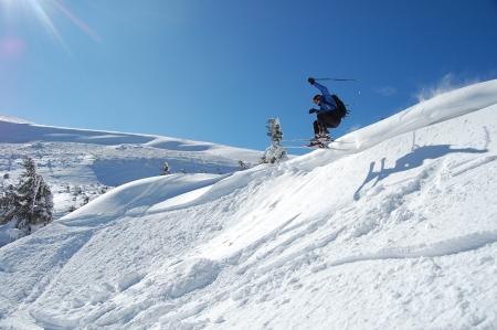 Skier jumps from a cliff in snow powder  Ukraine, Carpathians, Dragobrat