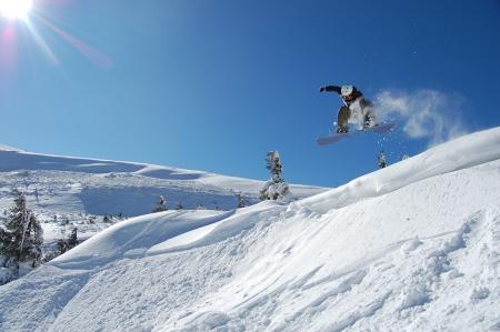 snowboarding: Snowboarder jumping from a cliff in snow powder  Ukraine, Carpathians, Dragobrat