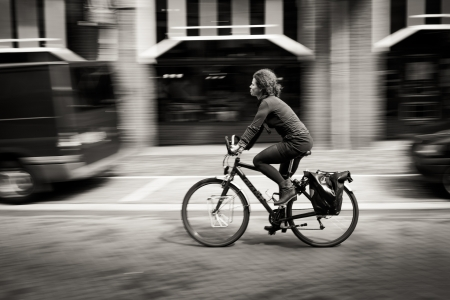 woman riding a bicycle down the street. Amsterdam. Black and white. Netherlands