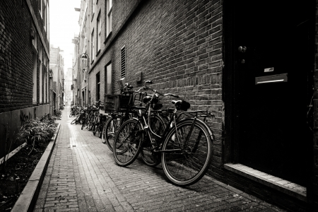 Old bicycles parked on a narrow street in Amsterdam. Black and white. Netherlands