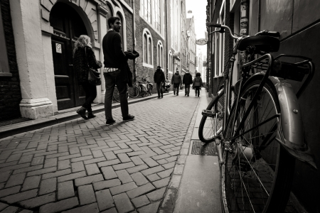 silhouette of cyclist on the street passing bike route sign. Black and white. Netherlands, Amsterdam