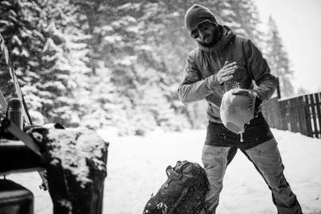 Young man in the snow forest shake off snow from helmet