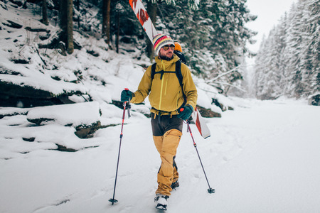 Young man with ski walking in the snow forest Banque d'images