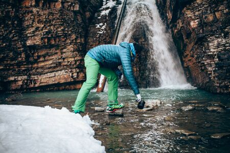 Young professional male tourist collects water from a mountain riverin winter. White waterfall and beautiful texture of rocks on background.Travel, trekking  and active life concept. Hiking, camping equipment.