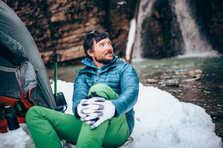 Young professional male tourist is sitting in the mountains near the river in winter. White waterfall and beautiful texture of rocks on background.Travel, trekking  and active life concept. Hiking, camping equipment. Banque d'images