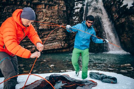 Two young professional male tourists are preparing to camp in the mountains near the river in winter. White waterfall and beautiful texture of rocks on background.Travel, trekking  and active life concept with team. Hiking, camping equipment.