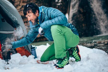 Young professional male tourist is preparing food and hot drinks in the mountains near the river in winter. Travel, trekking  and active life concept. Hiking, camping equipment.