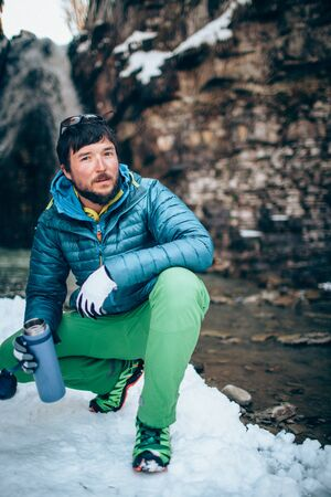 Young professional male tourist is drinking in the mountains near the river in winter. White waterfall and beautiful texture of rocks on background.Travel, trekking  and active life concept. Hiking, camping equipment.