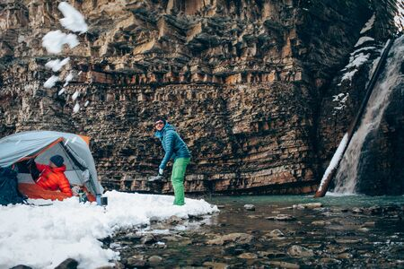 Two young professional male tourists are preparing food and hot drinks in the mountains near the river in winter. White waterfall and beautiful texture of rocks on background. Travel, trekking  and active life concept with team. Hiking, camping equipment.