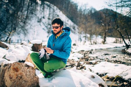 Young male tourist puts on gloves near a river in the mountains.Beautiful winter landscape with snow covered banks and trees on background. Climbing, trekking, active life, camping concept.