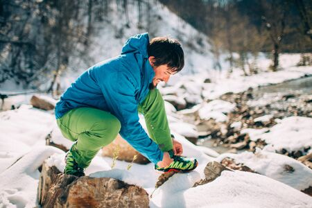 Young male tourist ties shoe laces near a river in the mountains.Beautiful winter landscape with snow covered banks and trees on background. Climbing, trekking, active life, camping concept.