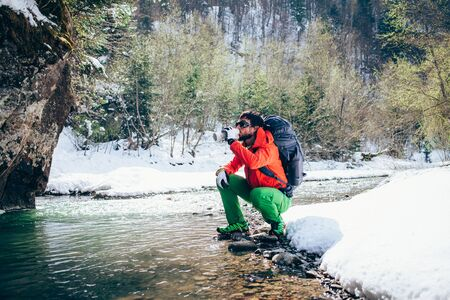 Young male tourist drinks fresh water from a river in the mountains.Beautiful winter landscape with snow covered banks and trees  on background. Climbing, hiking, trekking, active life concept. Banque d'images