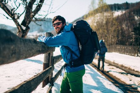 Young male tourist is resting near a fencing in the mountains. He has a happy smile on his face. Beautiful winter landscape with snow covered road on background. Climbing, trekking active life concept