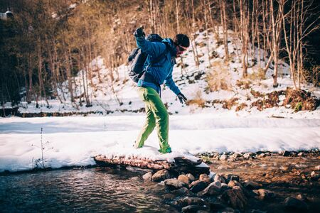 Male tourist �rosses a river in the mountains. Beautiful water with snow covered rocks on background. Climbing, trekking, hiking and active life concept.