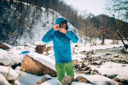 Young male tourist straightens his jacket near a river in the mountains.Beautiful winter landscape with snow covered banks and trees on background. Climbing, trekking, active life, camping concept.