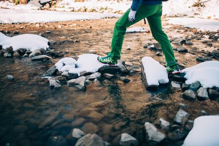 Male tourist �rosses a river in the mountains. Only the legs are visible.Beautiful water with snow covered rocks on background. Climbing, trekking, hiking and active life concept.