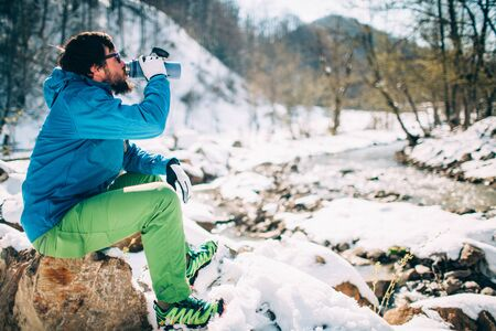 Young male tourist drinks hot coffee from a near a river in the mountains. Beautiful winter landscape with snow covered banks and trees on background. Climbing, trekking, active life concept