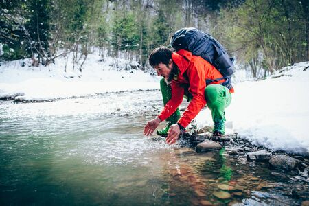 Young male tourist washes his face with river water in the mountains.Beautiful winter landscape with snow covered banks and trees on background. Climbing, hiking, trekking, active life concept. Banque d'images