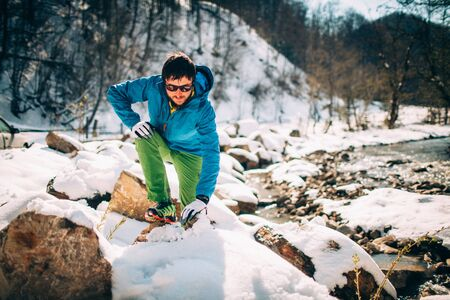 Young male tourist warms up before trip near a river in the mountains.Beautiful winter landscape with snow covered banks and trees on background. Climbing, trekking, active life, camping concept.