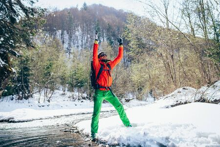 Young male tourist raises his hands near a river in the mountains.Beautiful winter landscape with snow covered banks and trees  on background. Climbing trekking  and active life concept.