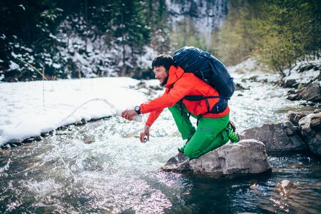 Young male tourist fillings water into the bottle from a river in the mountains.Beautiful winter landscape with snow covered banks and trees  on background. Climbing, trekking, active life concept.